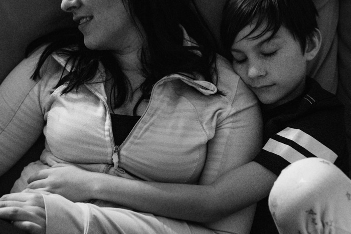 the magic of a boy snuggled into woman closing his eyes