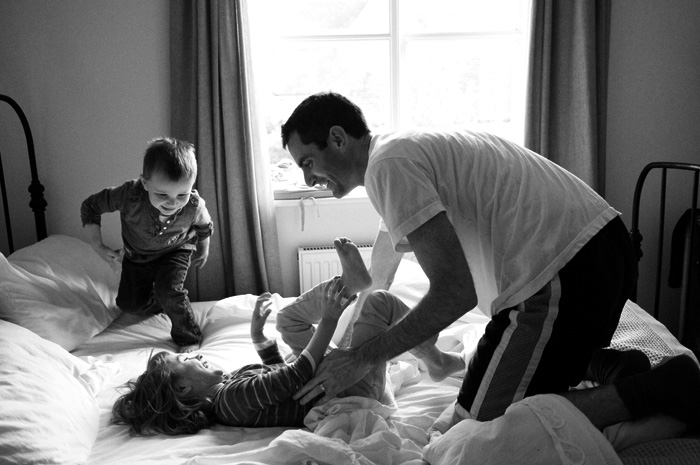 dad simplifying life by tickling two children on a bed