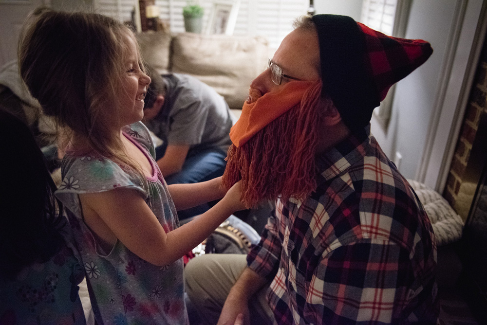 dad and daughter laughing and playing with a costume beard